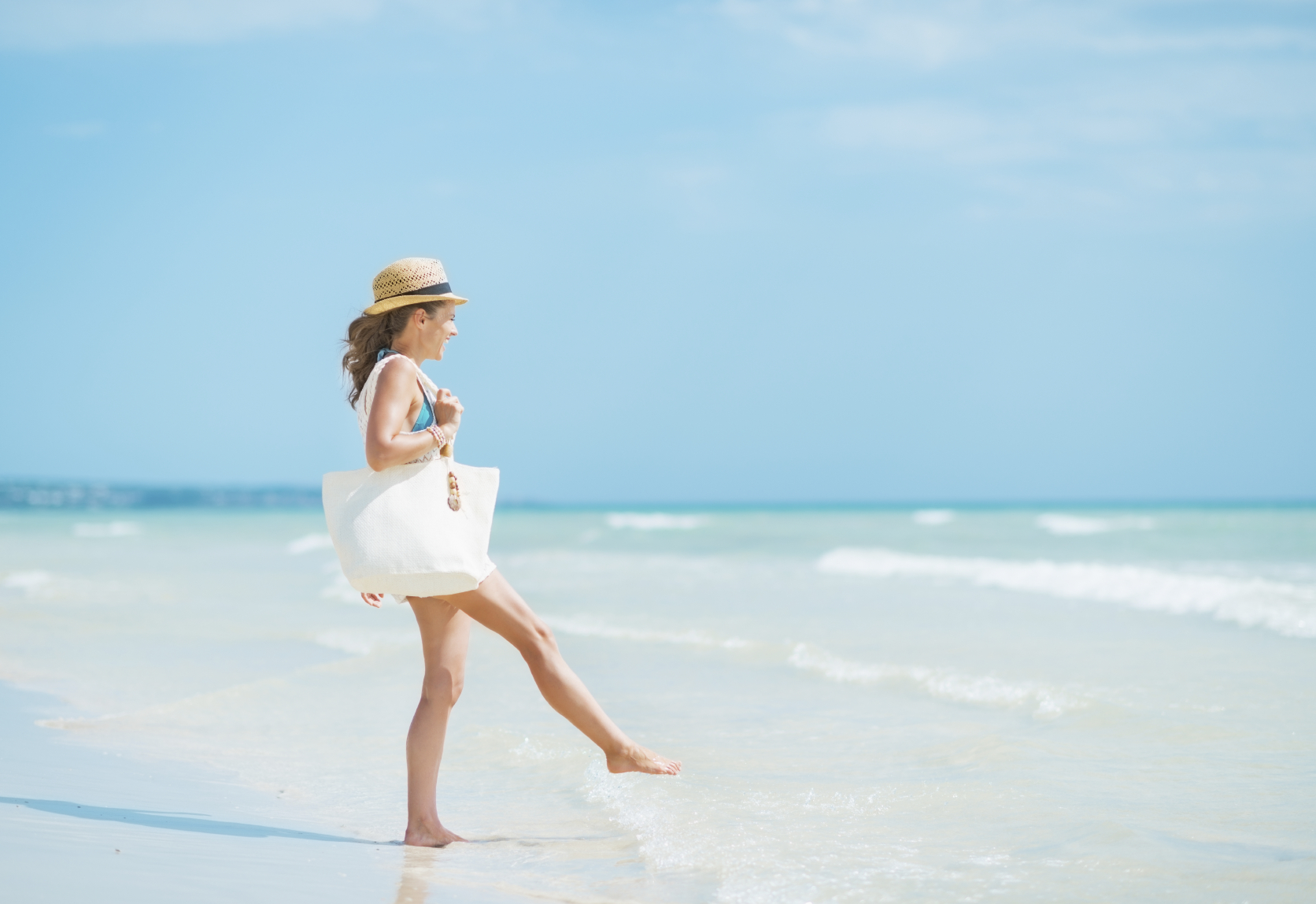 Young woman with hat and bag having fun time on sea coast