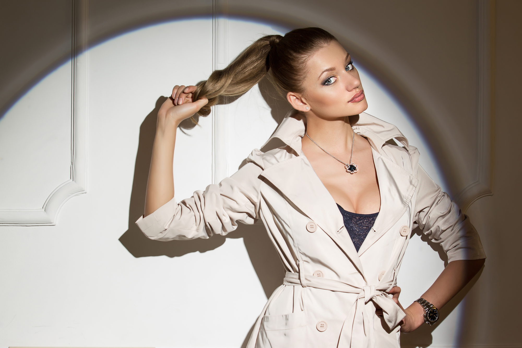 Portrait of a stylish girl in the studio. Model is wearing a cloak. Beautiful hair tied in a ponytail.