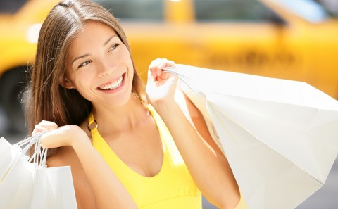 Shopping woman in New York City. Beautiful happy summer shopper holding shopping bags walking outside smiling with yellow taxi cab in background. Multiracial Asian Caucasian model on Manhattan, USA.