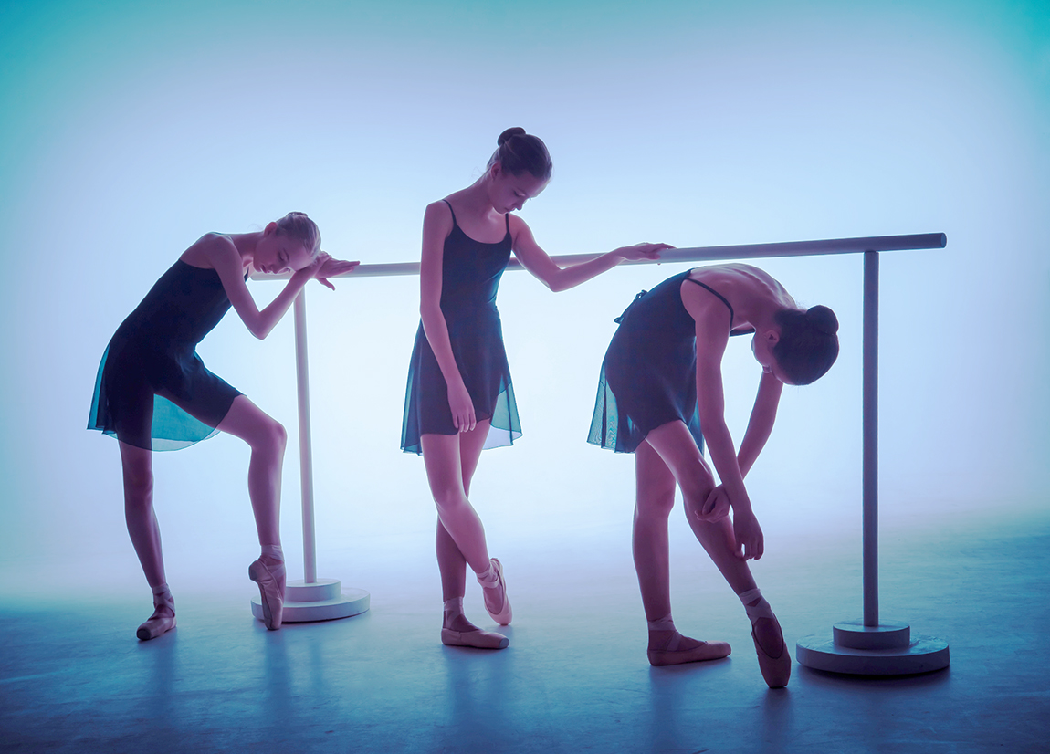The silhouettes of young ballerinas stretching on the bar on blue background