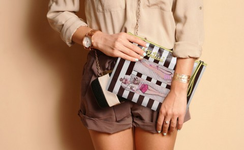 Fashionable woman with  stylish black and white clutch , accessories, watch . Elegant outfit silk blouse and  brown shorts